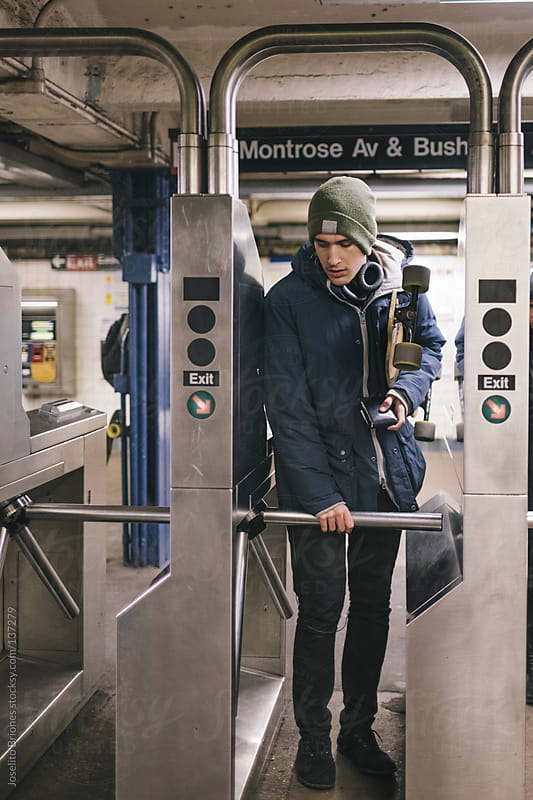 Young Male Student Entering New York Subway through Turnstile by Joselito Briones for Stocksy United