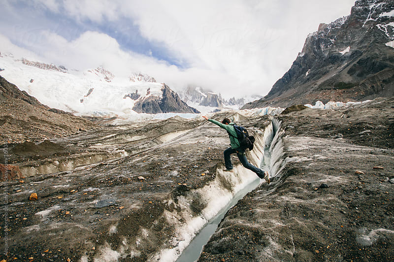 Young man jumping a gap on ice on a glacier in Patagonia, Argentina by Alejandro Moreno de Carlos for Stocksy United