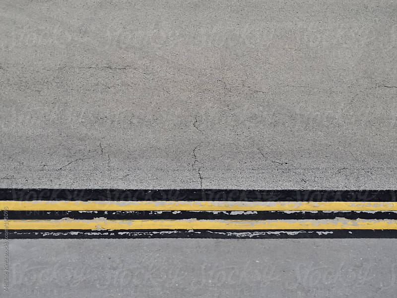 Yellow and black lines on an airport tarmack by Melanie Kintz for Stocksy United