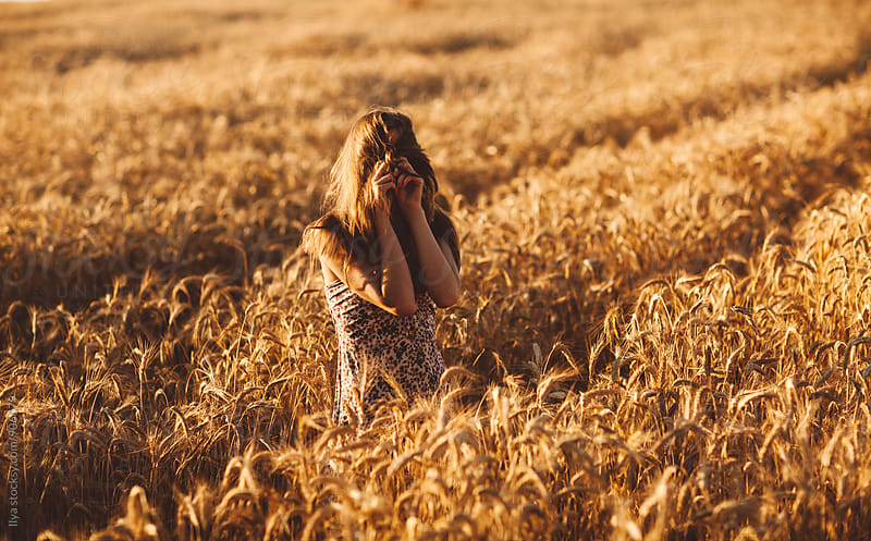 Young woman in summer dress in wheat field by Ilya for Stocksy United