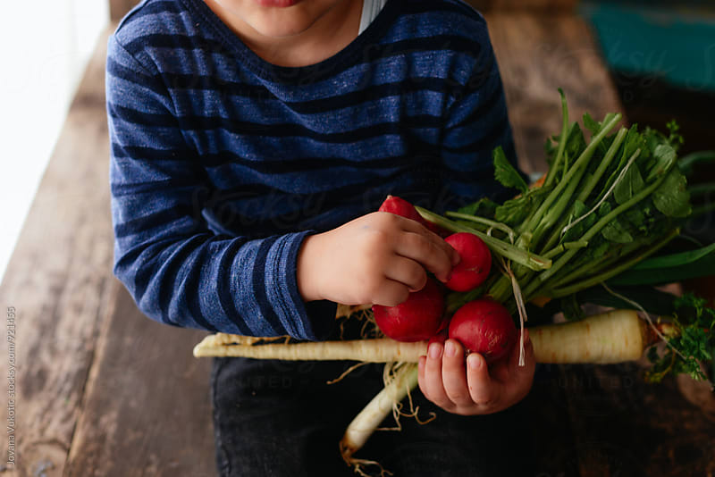 Boy and vegetable by Jovana Vukotic for Stocksy United