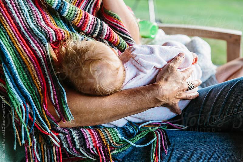 Baby Breast Feeding on Porch by Raymond Forbes LLC for Stocksy United