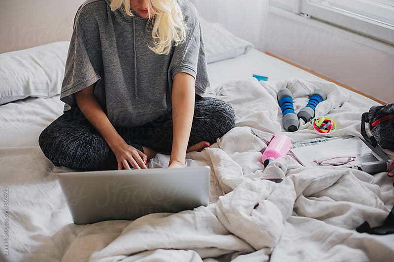 Blonde Woman Working on a Laptop in the Bedroom by Lumina for Stocksy United