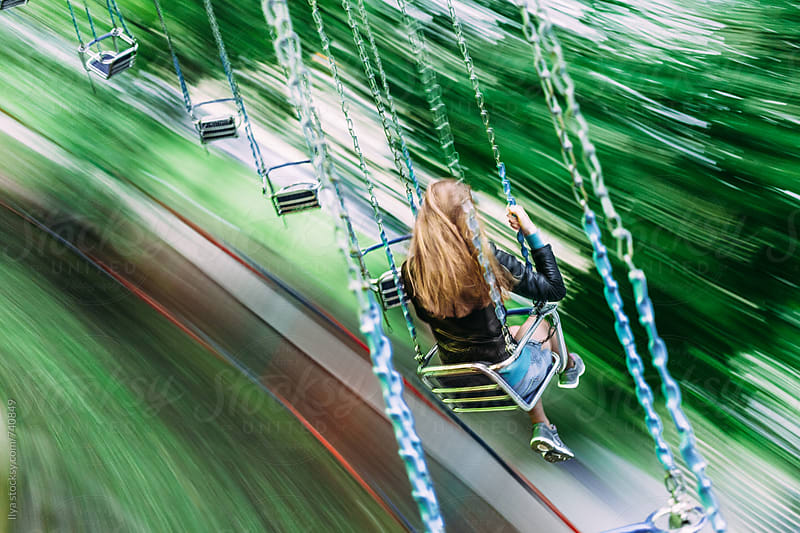 Young woman riding on a swing carousel in amusement park smiling by Ilya for Stocksy United