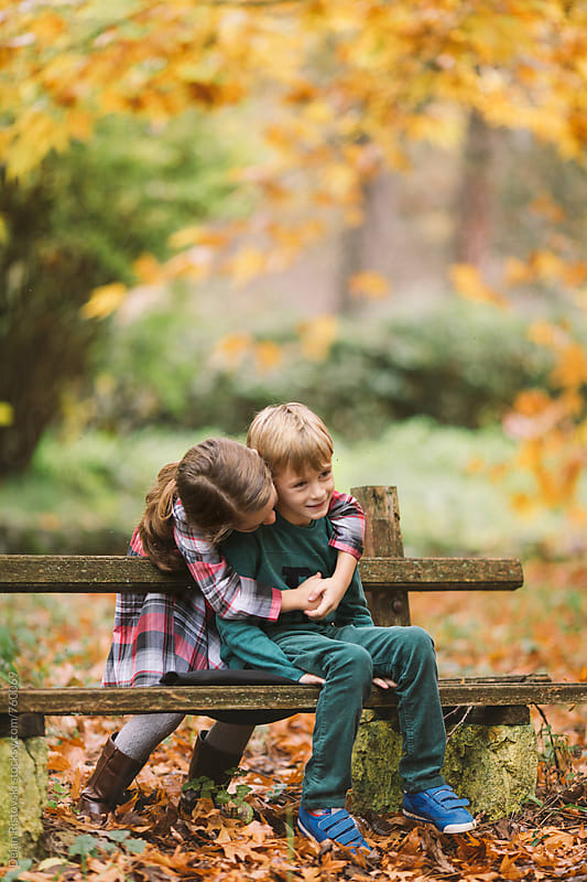 Siblings hugging in nature by Dejan Ristovski for Stocksy United