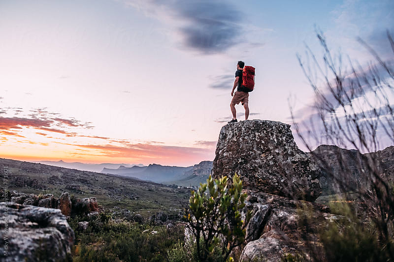Hiker on a rocky outcrop facing the sunset by Micky Wiswedel for Stocksy United