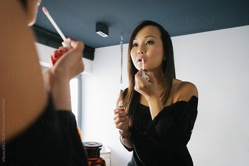 Young Asian Woman Applying Make Up in Bathroom by VISUALSPECTRUM for Stocksy United