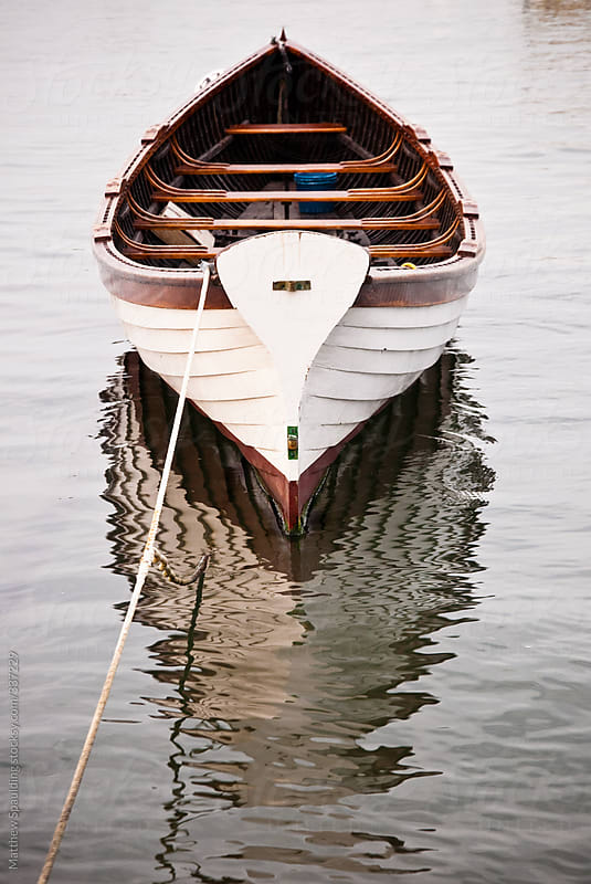 Wooden boat floating peacefully on water by Matthew Spaulding for Stocksy United