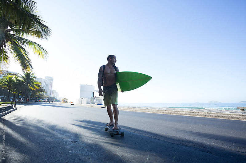 Surfer on skateboard. Ipanema beach. Rio by Hugh Sitton for Stocksy United