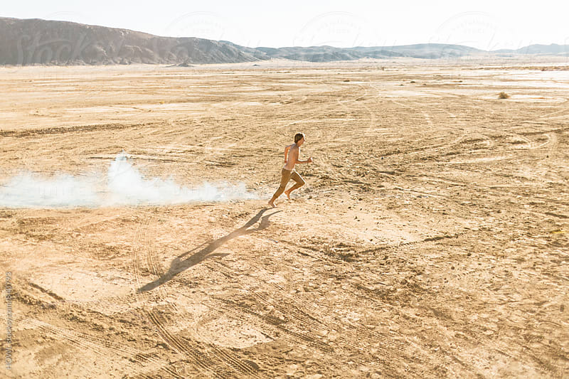 A young man running shirtless in the desert  by HOWL for Stocksy United