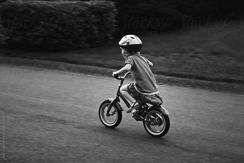 young girl riding bicycle by Jess Lewis for Stocksy United
