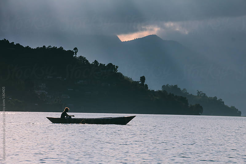 Canoe boat on a lake at sunset, Pokhara, Nepal by Alejandro Moreno de Carlos for Stocksy United