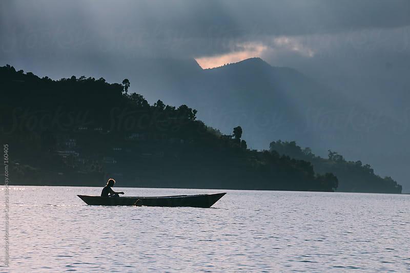 Canoe boat on a lake at sunset, Pokhara, Nepal by Alejandro Moreno de Carlos for Stocksy United