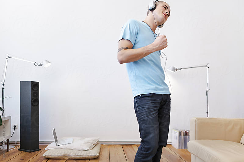 Young Man Having Fun Listening to Music with Headphones by Joselito Briones for Stocksy United