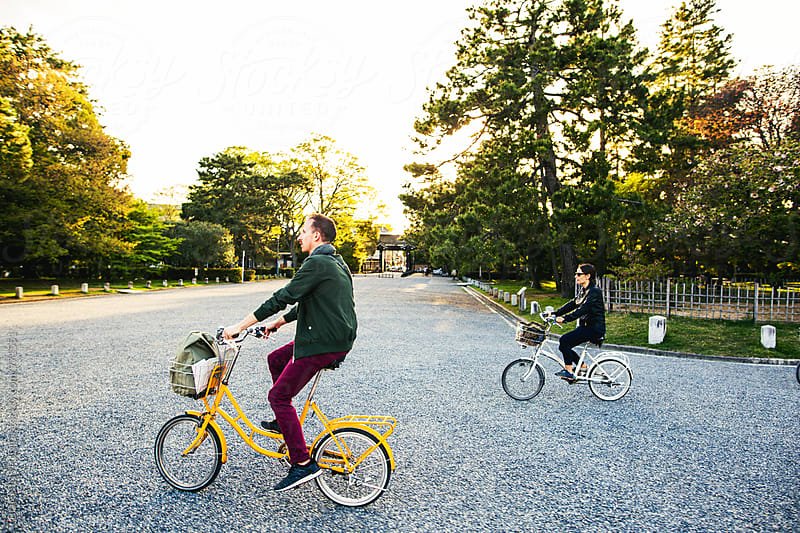 Side view of friends riding their bicycle in park. by BONNINSTUDIO for Stocksy United