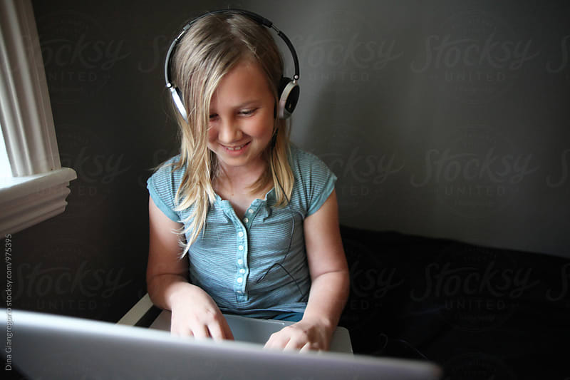 Wide Angle View Of Girl Wearing Headphones On Laptop by Dina Giangregorio for Stocksy United