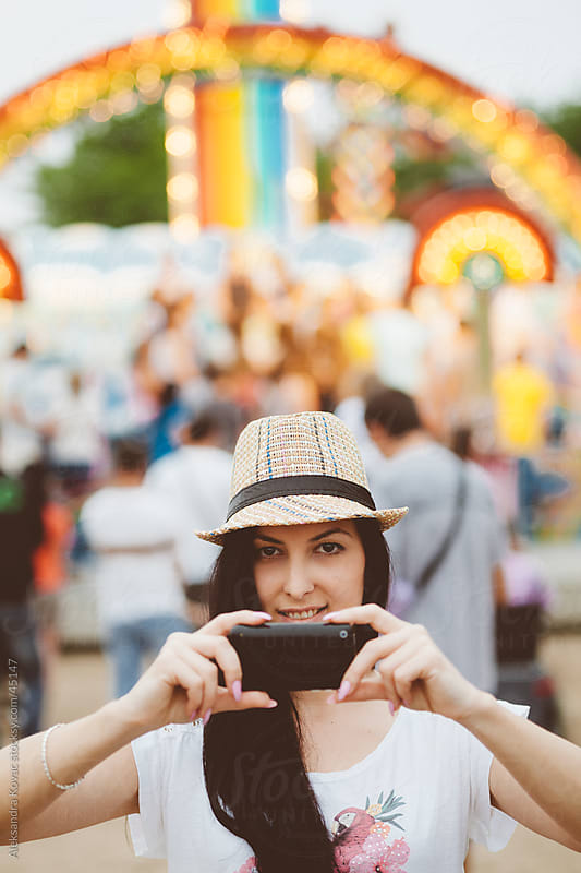 Young woman photographing with smart phone at amusement park by Aleksandra Kovac for Stocksy United