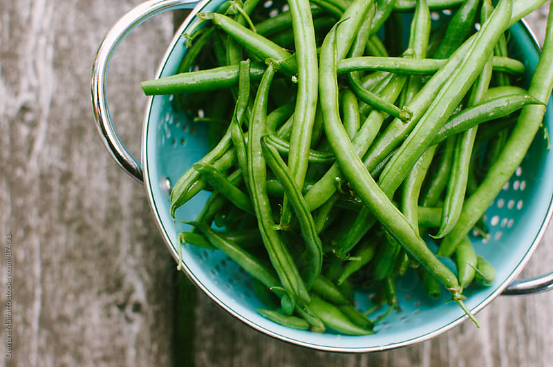 fresh green beans in a colander by Deirdre Malfatto for Stocksy United