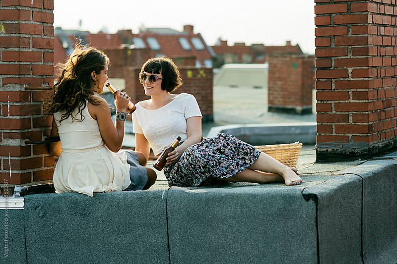 Female couple on city rooftop by VegterFoto for Stocksy United