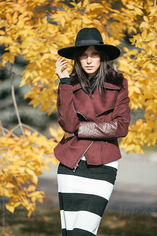 A woman touching her wide brimmed hat shading her face on a fall day by Ania Boniecka for Stocksy United