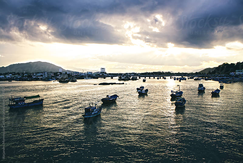 Sunset in fishermans harbour with boats in Nha Trang city, Vietnam by Alejandro Moreno de Carlos for Stocksy United