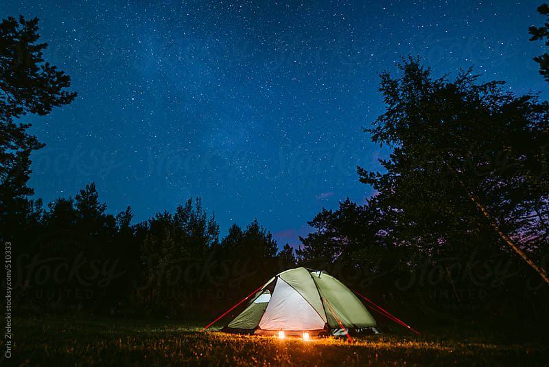 an illuminated tent in the night under stars by Christian Zielecki for Stocksy United