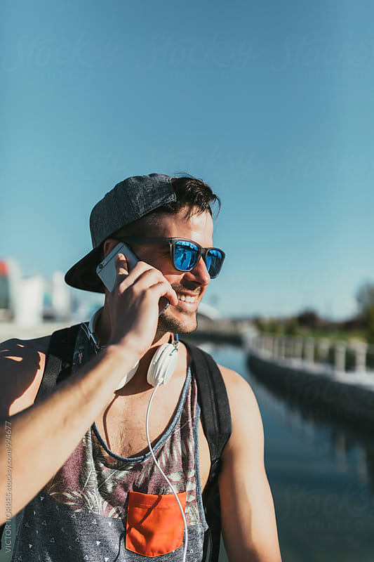 Young Handsome Man Talking by Phone in a Sunny Day by VICTOR TORRES for Stocksy United