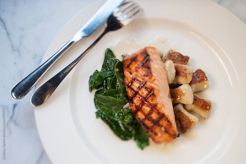 Grilled Salmon with Spinach and Gnocchi by Lindsay Upson for Stocksy United
