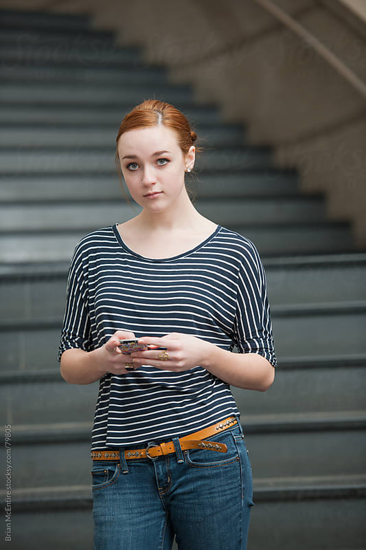 Senior Girl Using Phone on Steps in High School by Brian McEntire for Stocksy United