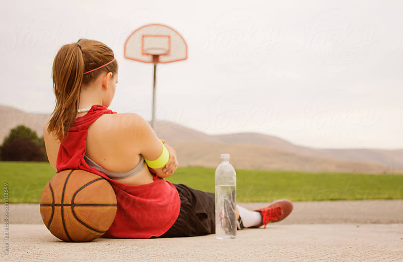 Girl sits with basketball on the basketball court by Tana Teel for Stocksy United