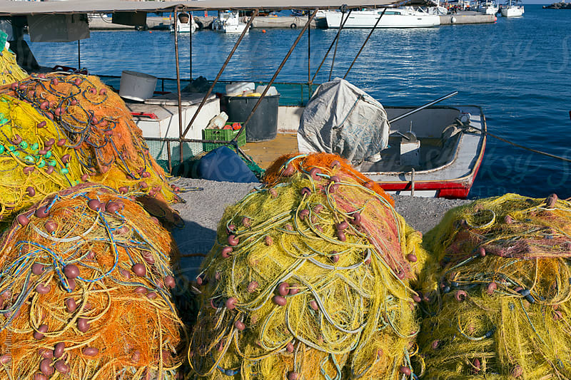 Bright fishing nets beside a boat in a harbour. Santorini, Greece by Paul Phillips for Stocksy United