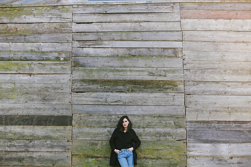 Young brunette leaning on a wooden wall  by Marija Kovac for Stocksy United