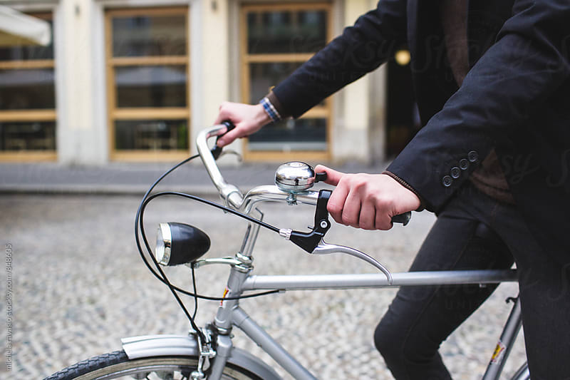 Man on the handlebars of his bicycle by michela ravasio for Stocksy United