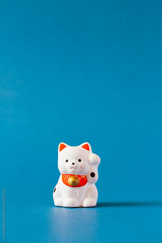 Famouse Japanese beckoning cat made with porcelain on blue by Laura Stolfi for Stocksy United