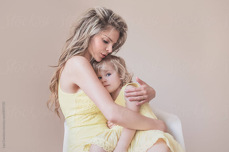 Mother holding her daughter in her arms by Lea Csontos for Stocksy United