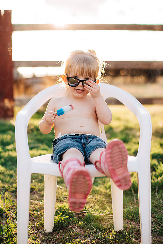 Small child wearing sunglasses in lawn chair by Jessica Byrum for Stocksy United