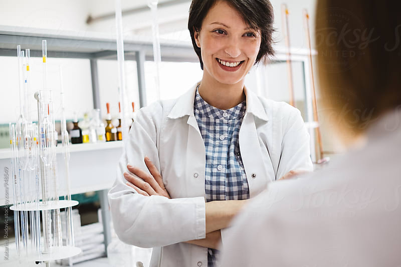 Pretty Female Chemist Talking With her Colleague by Katarina Radovic for Stocksy United