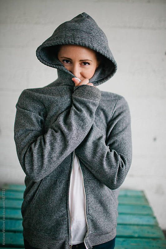 Woman looks at camera with hood over her head by Kristine Weilert for Stocksy United