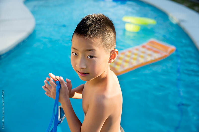 Cute asian boy getting ready to go swimming by Curtis Kim for Stocksy United