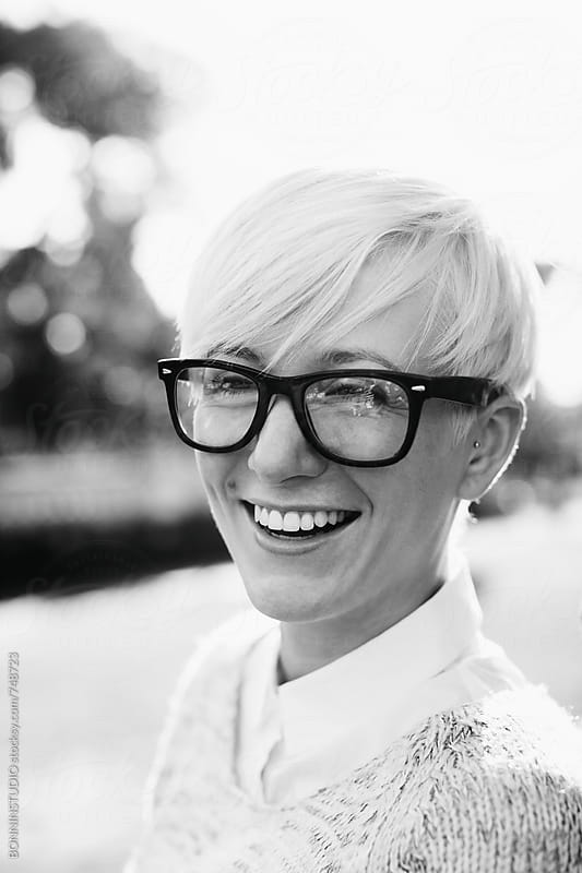 Smiling woman wearing glasses. Black and white photo. by BONNINSTUDIO for Stocksy United