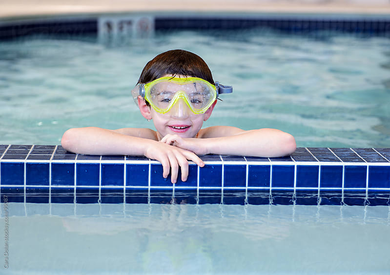 Boy wearing a diving mask rests on the edge of an indoor swimming pool by Cara Dolan for Stocksy United