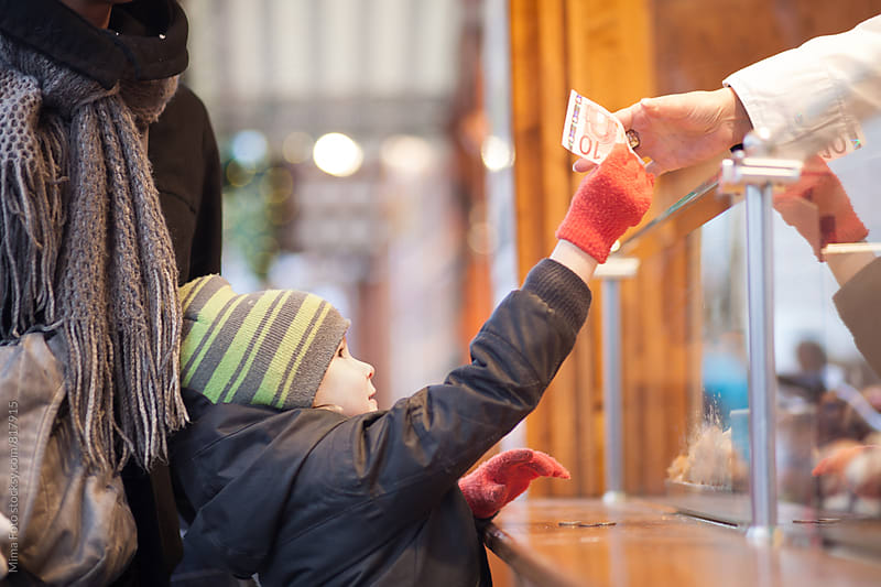Boy paying vendor at Christmas market by Mima Foto for Stocksy United