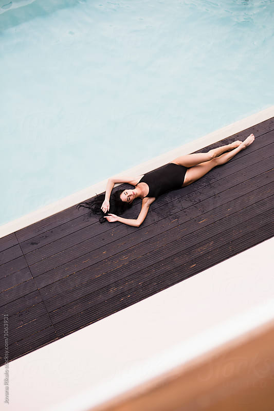 Attractive young woman sunbathing at the pool by Jovana Rikalo for Stocksy United