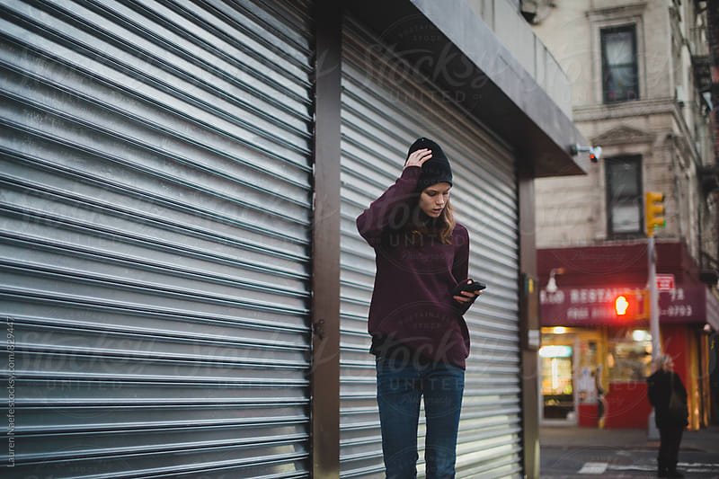 Young urban woman checking cell phone by Lauren Naefe for Stocksy United