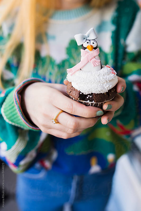 Young woman holding holiday cupcakes by Jovana Rikalo for Stocksy United