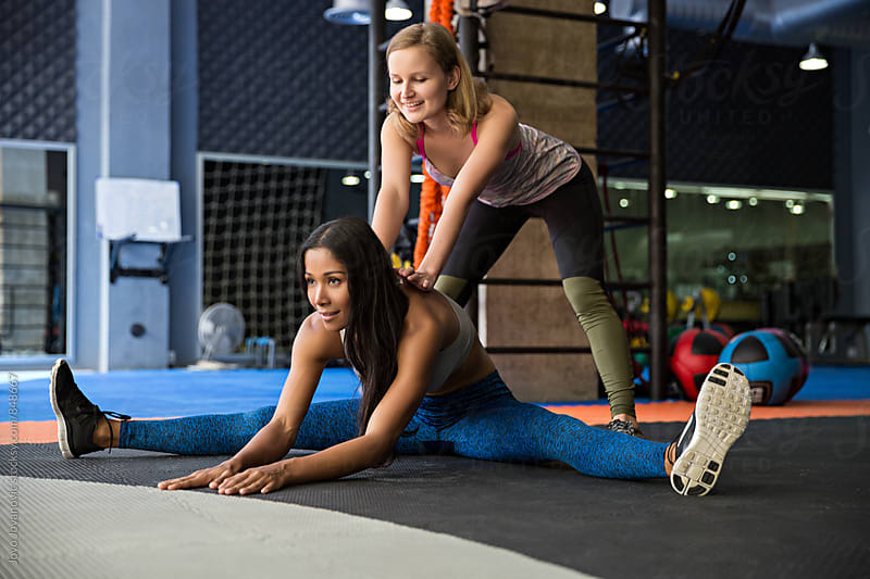 Workout friend helps a girl into a split by Jovo Jovanovic for Stocksy United