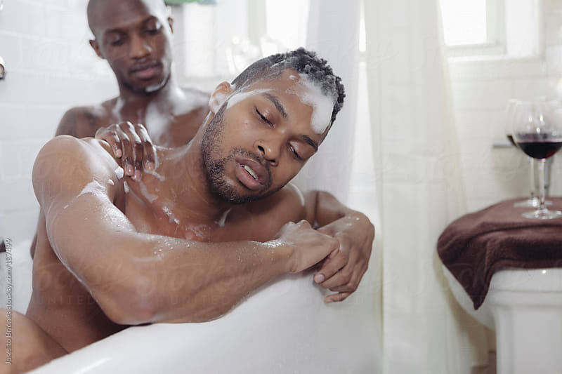 Gay Couple Giving Backrub while Bathing Together in a Bath Tub by Joselito Briones for Stocksy United