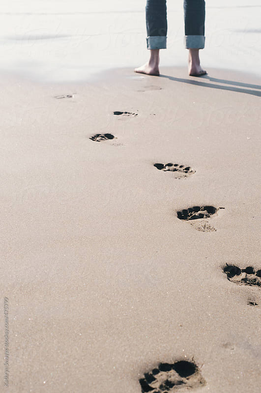 A woman's legs are seen by the waterfront with a series of footprints in the sand by Kathryn Swayze for Stocksy United