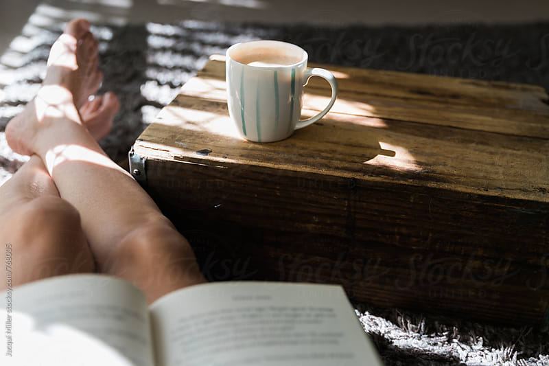 Woman with bare feet, relaxing indoors, with a coffee and a book by Jacqui Miller for Stocksy United