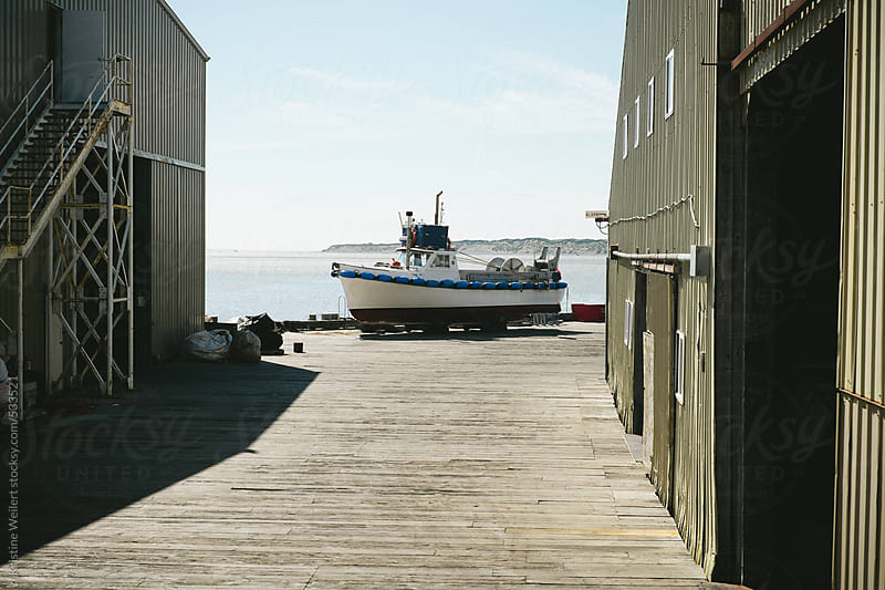 Fishing boat on the deck in a fishing town by Kristine Weilert for Stocksy United